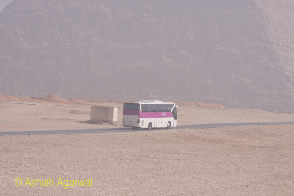 Closer view of a bus carrying tourists from the Panorama point to the Great Pyramid, with the base of the Pyramid being visible