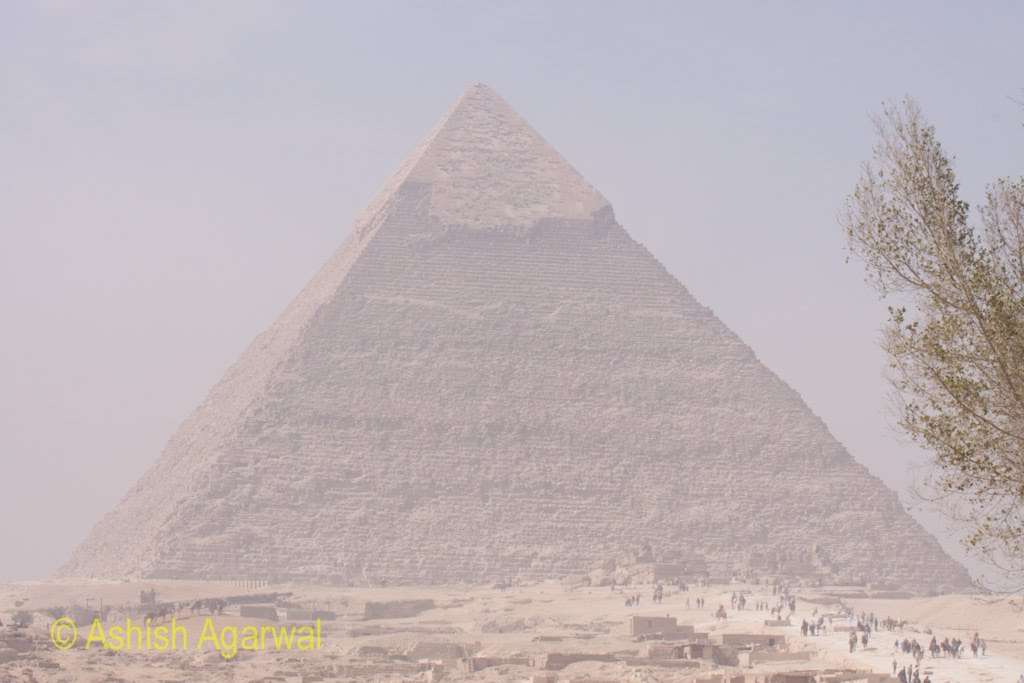 A view of the Great Pyramid along with tourists at the base of the Pyramid