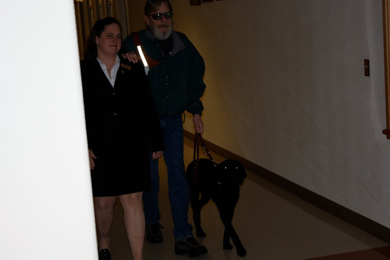 Mike walks down the hall with his hand on an instructor's shoulder heeling Millie at his side