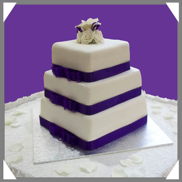 white sugarcrafted roses and purple ribbons to accentuate wedding cakes