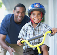 picture of dad teaching son to ride a bike