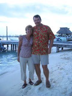 Nan and John at Brisas Grill on Isla Mujeres, with Ballyhoo in background