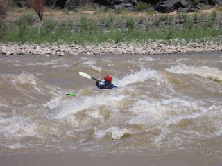 Aspen Kayak Academy student in the standing wave at 'Little D' rapids in Westwater Canyon