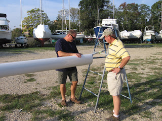 John Kretschmer and John Simonton examine Whispering Jesse's freshly painted mast