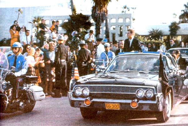 11/18/63: cycles and SA Sulliman beside JFK; close press/ photographers; Boring and military aide