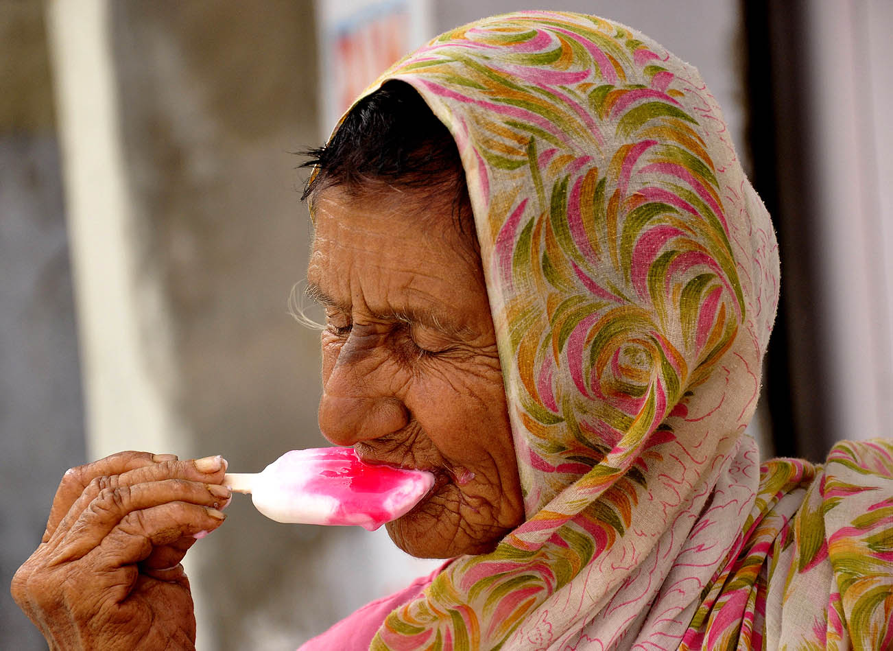 world with my eyes: an old lady enjoying an ice-candy on a hot day