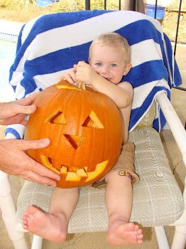 "Kaleb holding the pumpkin he ""helped"" his daddy carve."