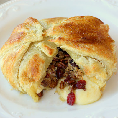 Cranberry and Pecan Brie En Croute - a festive appetizer that gets devoured in minutes. the-girl-who-ate-everything.com
