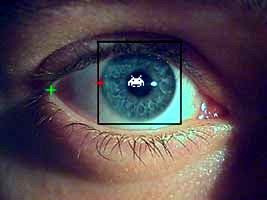 Image of a computer mock up of an eye being tracked with a Space Invader reflected in the eye.