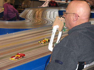 Image of a man racing a Scalextric style slot-car around a minature track using a chest mounted chin controller.