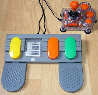 Image of a three colourful adjoined pedals and a chunky transparant joystick - accessible gaming set-up.