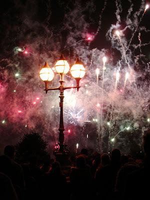 Image of fireworks over a London Bridge - purple smoke difusing an old fashioned street light.