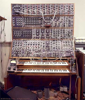 Image of a bonkers old Synthesiser with a jumbled mass of leads hanging all over it.