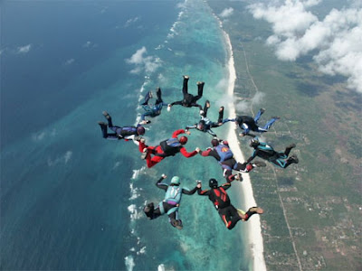 Image of 10 skydivers forming a ring falling to earth over a blue coast-line.