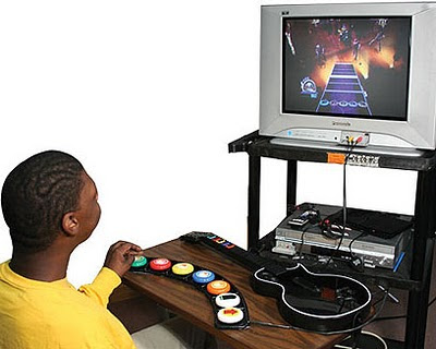 Image of a young man playing Guitar Hero on an array of seven medium sized multi-coloured accessibility switches, arranged in an arc.