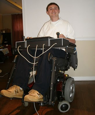 Quasicon Axis Basile. Josh Basile grinning with his large Quasicon accessible game controller, positioned on his wheelchair tray.