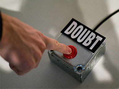 Image of a man's hand reaching out to press a red push button, above which is the word 'Doubt'.