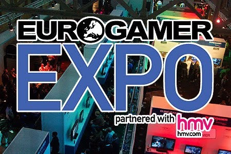 High up photo of the EuroGamer Expo hall in 2009, full of people and games machines. The text reads 'EuroGamer Expo 2010, partnered with HMV. Links with the attendance of the Accessible GameBase.