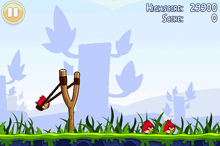 Image of Angry Birds, iOS game, where you sling shot a bird back to crash into pigs protected by flimsy structures.