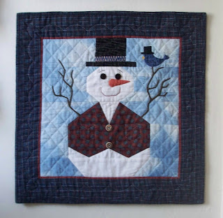 quilted wallhanging of a snowman wearing a tophat and two button plaid vest. His arms are made from twigs and a bluebird, also wearing a tophat is resting on one of the arms