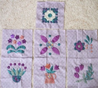 seven applique blocks of flowers and leaves in purples and greens