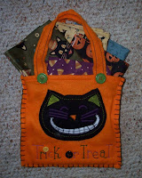 Orange felt bag with black cat on front containing five fat quarters with Halloween prints