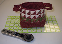 red fabric basket about five inches wide using three rows of half square triangles that Shirley was throwing away