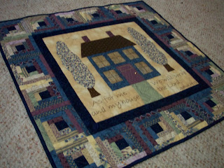 wallhanging with appliqued house and log cabin border