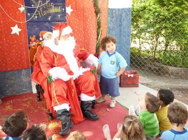 Papai Noel conversando e distribuindo balinhas para as crianças