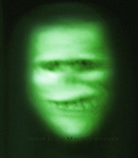 green glowing ghostly face with malevolent grin