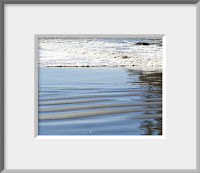A framed photo of shimmering ripples of wet sand and foamy blue surf advancing up the beach capture the aura of the wild coast of Olympic National Park.