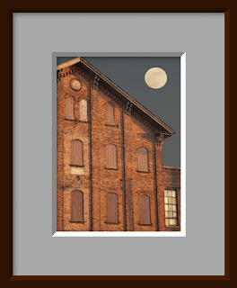 An old brick warehouse under a full moon.
