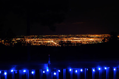A night landscape of city lights and blue lights on a deck.