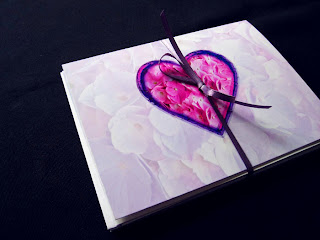 A Valentine card with a heart full of pink flower petals on a pale lavender background of petals.