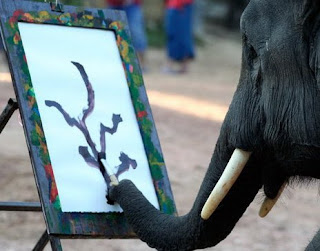 funny elephant photo painting a picture of a tree with a paintbrush in his trunk very smart