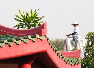 Worker on the roof behind the Karon Plaza temple