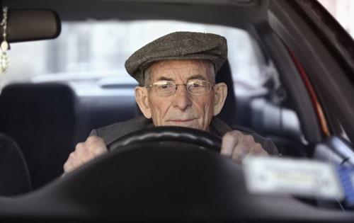 un uomo anziano con il cappello al volante