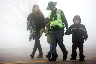State Trooper L.C. Block, center right, holds the hands of Carter Raymond, far right, and his cousin Kyle Czarnik as Kyle's mother, Andrea Thorngren, holds her sons hand and they walk away from the crash scene on Interstate 90 Sunday.(Photo by Leah L. Jones - State Journal)