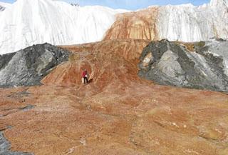 Un investigador posa sobre la superficie helada de Las cataratas de sangre. Science