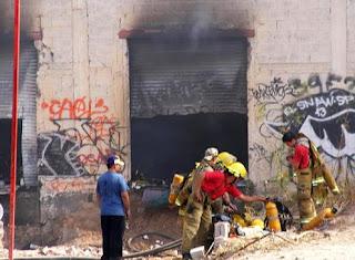 Miembros del cuerpo de bomberos trabajan en la fábrica de neumáticos donde se inició el incedio. EFE