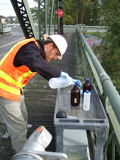 image of a man testing for toxic chemicals in river water samples