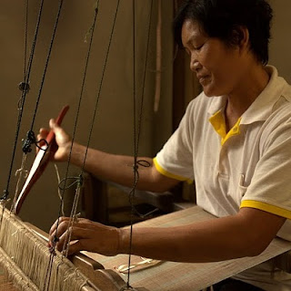 weaver at her traditional loom made from bamboo and tropical hardwood