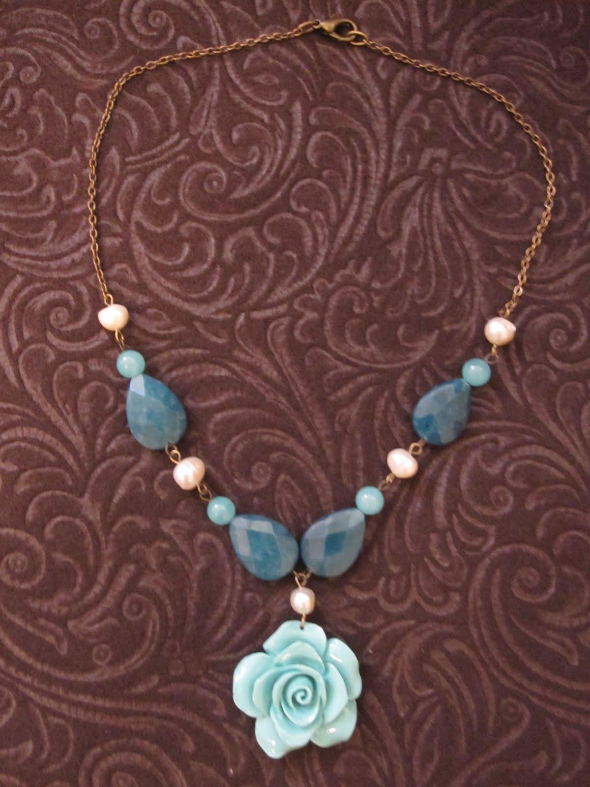 Collar corto en dorado antiguo con colgante de flor turquesa, cuentas pequeñas también turquesas, lágrimas de jade verde facetado, perlas de río y cadena en