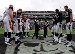 The Oakland Raiders and Cincinnati Bengals ready for a coin flip to determine possession in overtime