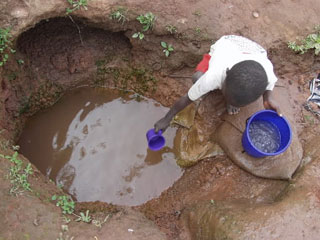 a young boy dips his pail to get drinking water from a muddy hole