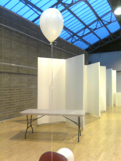empty display stands, lonely white balloon hovering in foreground