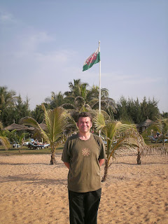 Rhys Hughes on beach in Africa with Welsh flag in background.