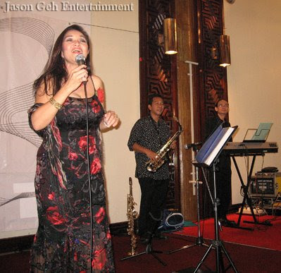 Image of a Jazz singer backed by two musicians