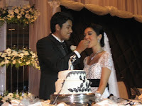 a photo of Yasir, the groom feeding Aainna, the bride during the cake cutting ceremony