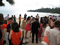 Guests chatting and having their cocktails by the beach